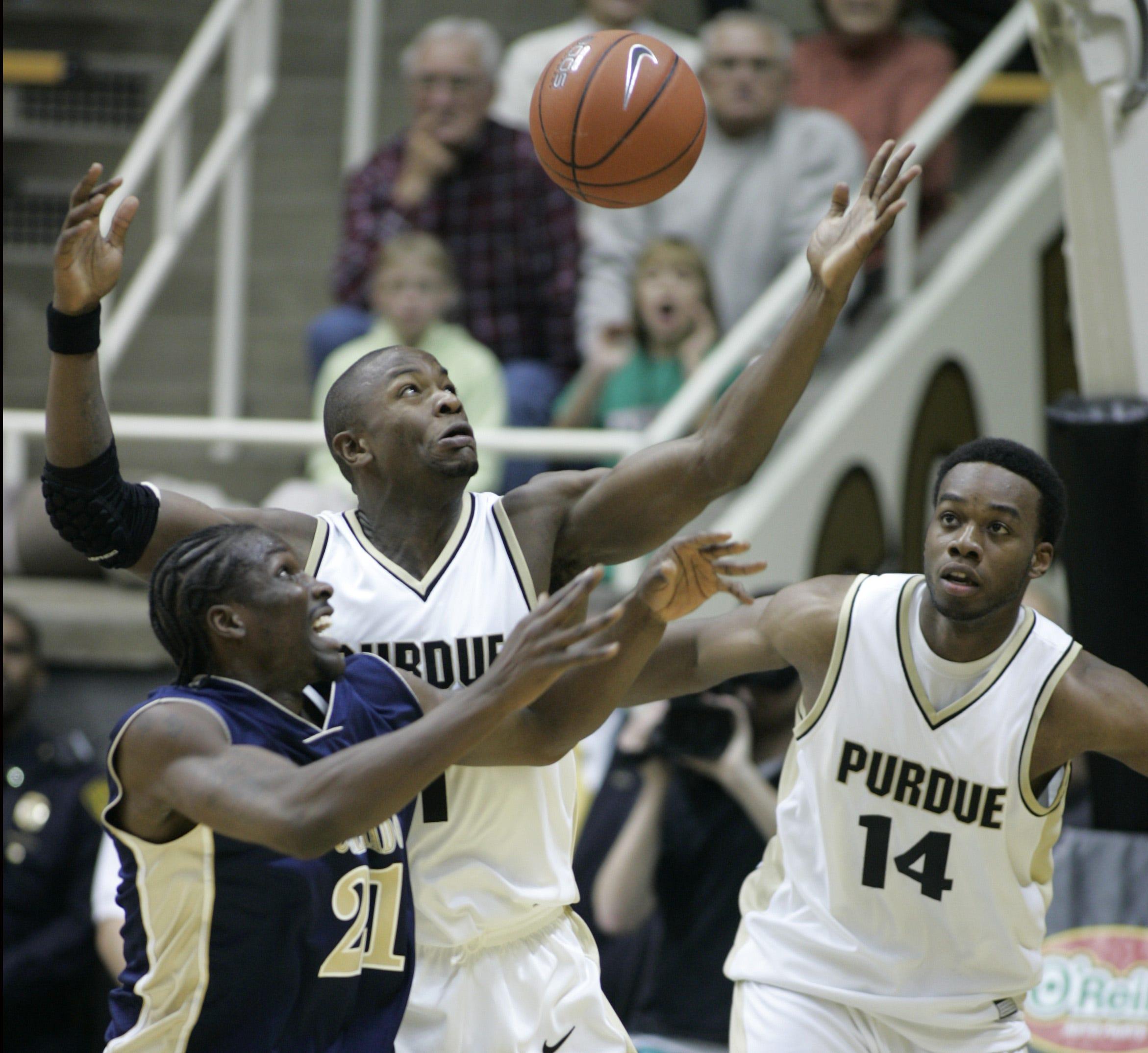 Purdue forward Gordon Watt, center, battles for a rebound.