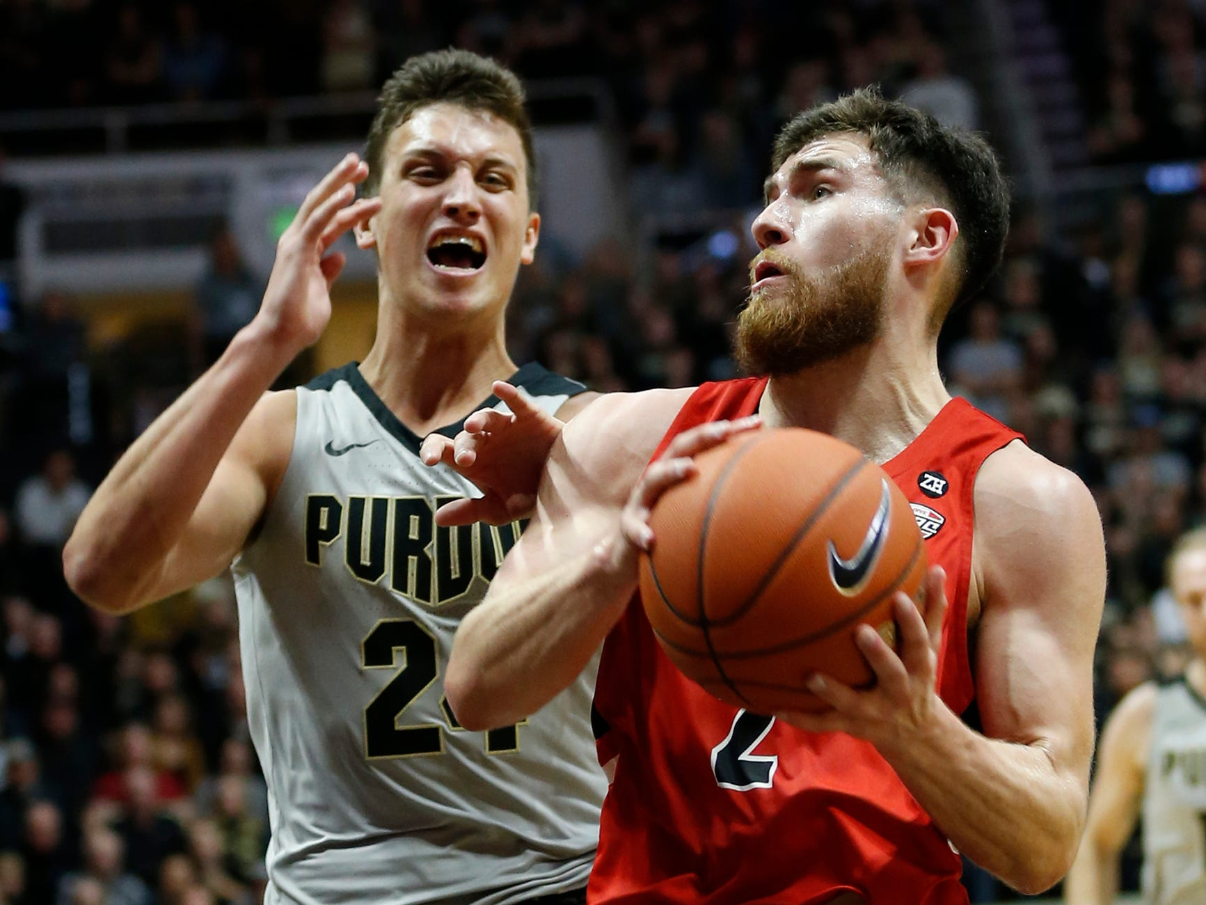Tayler Persons of Ball State gets past Grady Eifert of Purdue for a shot Saturday, November 10, 2018, at Mackey Arena. Purdue defeated Ball State 84-75.