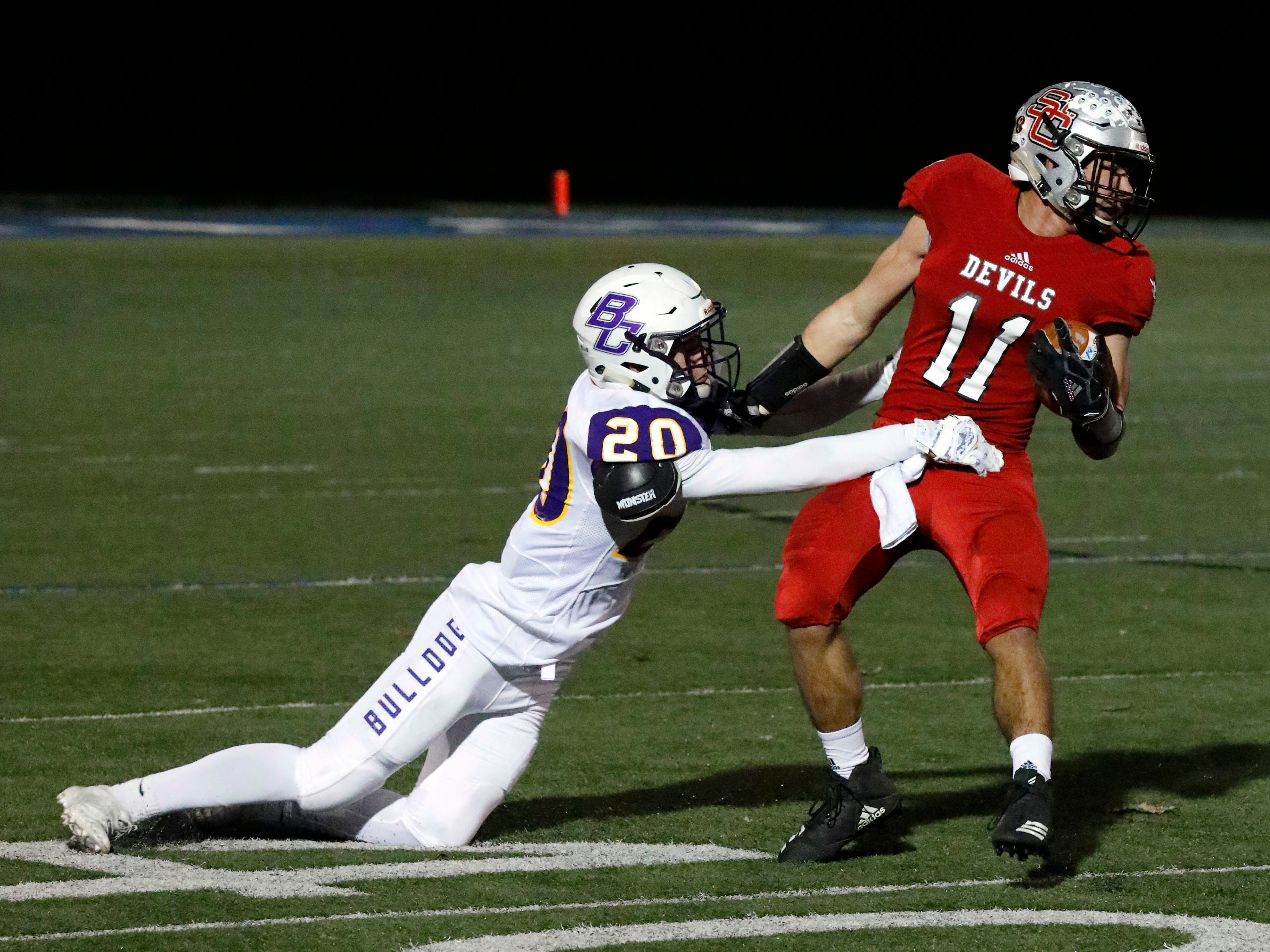 St. Clairsville's Kyle Storer tries to break free of a tackle from Bloom-Carroll's Gavin Powers Saturday night, Nov. 10, 2018, at Zanesville High School in Zanesville. The Bulldogs lost the regional semifinal game to St. Clairsville 41-14.