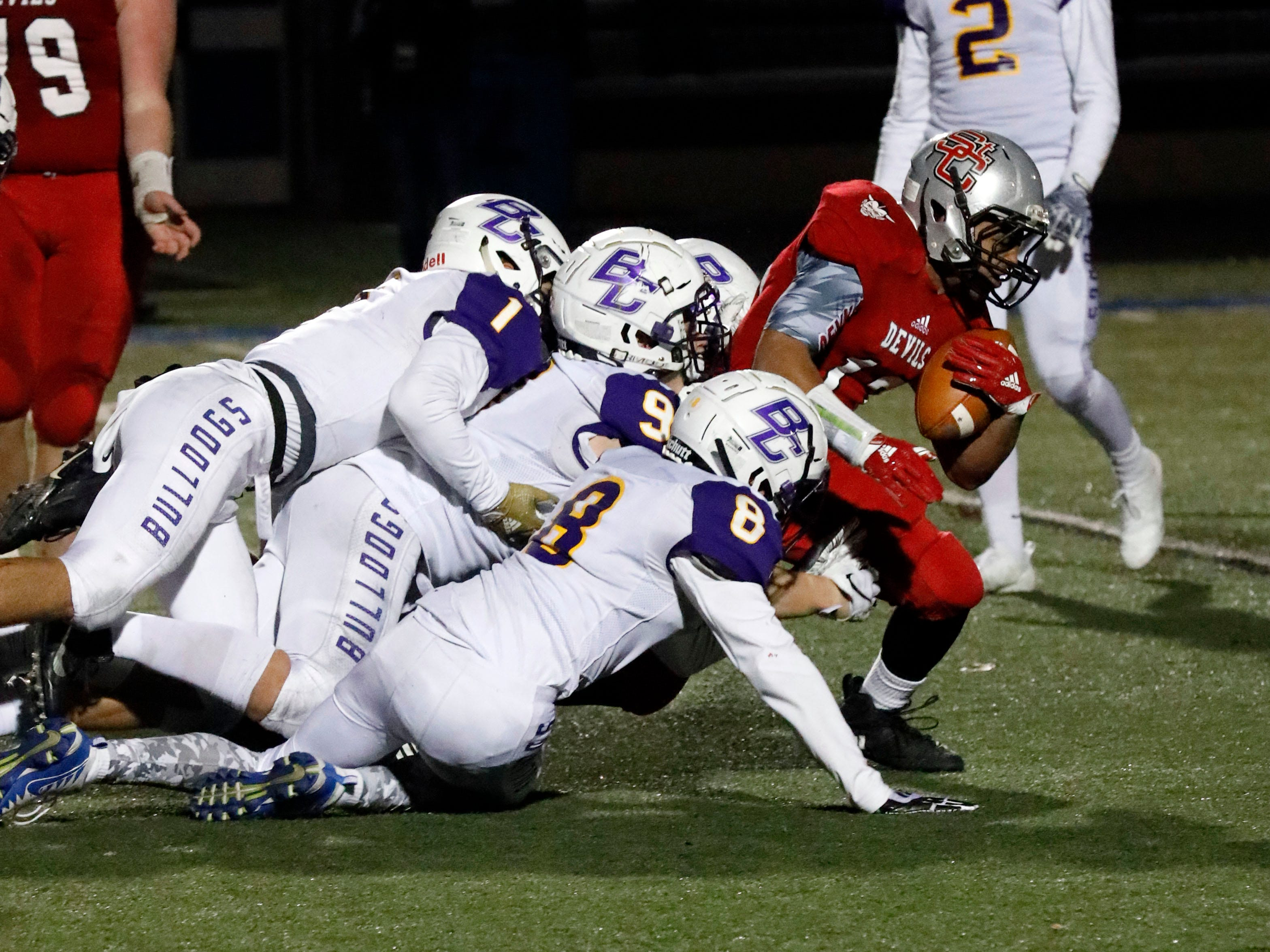 St. Clairsville's Jacob Jordan tries to break through a tackle by Bloom-Carroll players including Josh Evans (#1), Hobie Scarberry (#9) and Cody Harmon (#8) during Saturday night's game, Nov. 10, 2018, at Zanesville High School in Zanesville. The Bulldogs lost the game 41-14.