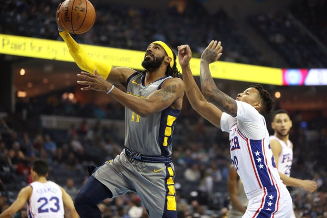 Grizzlies guard Mike Conley lays the ball up past 76ers guard Markelle Fultz during Saturday's game.