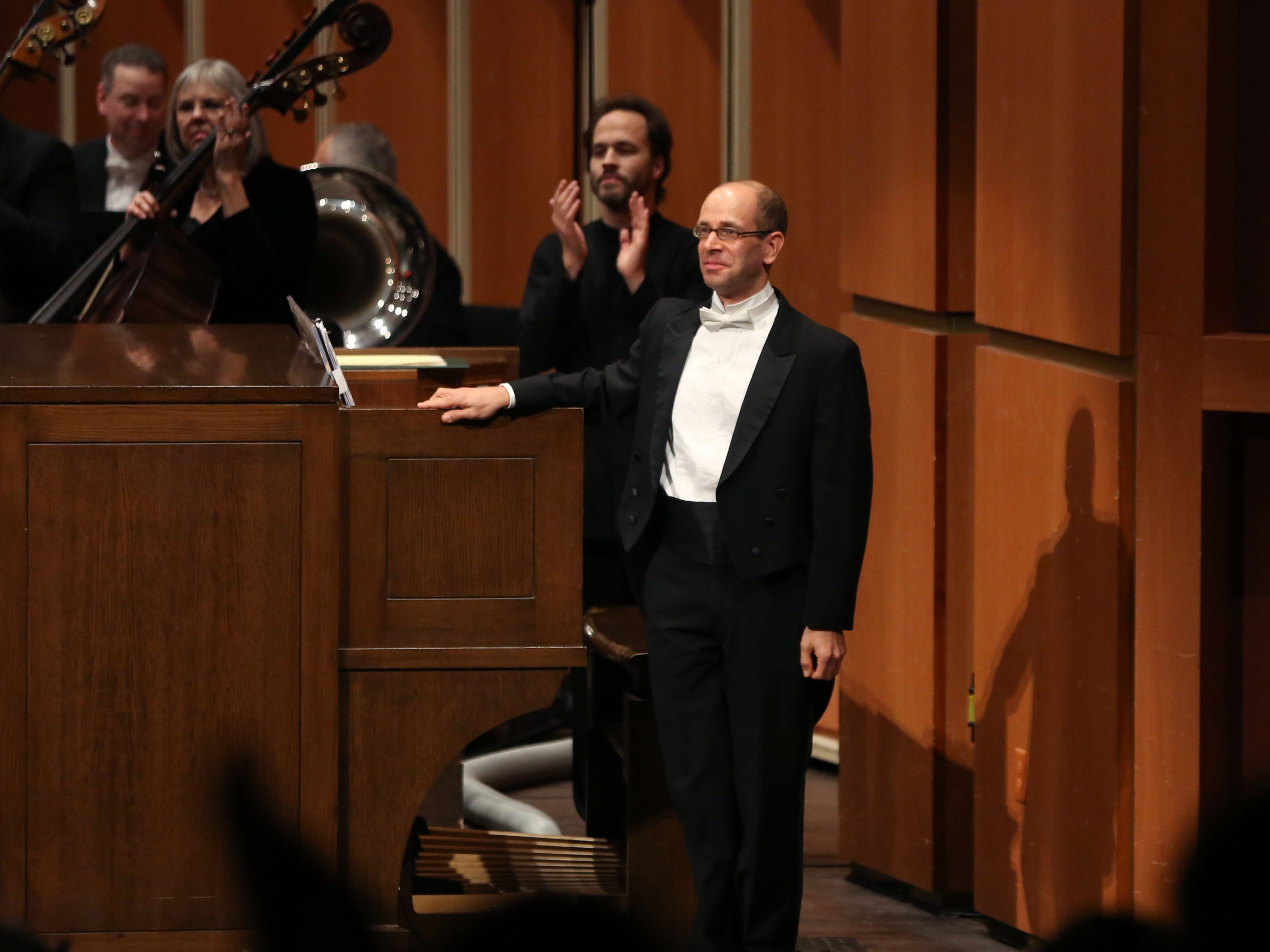 Conductor Johannes Debus, in back, leads the applause for Milwaukee Symphony and organist David Jonies after their performance of Camille Saint-Saens' Symphony No 3 in C minor Saturday night at the Marcus Center.
