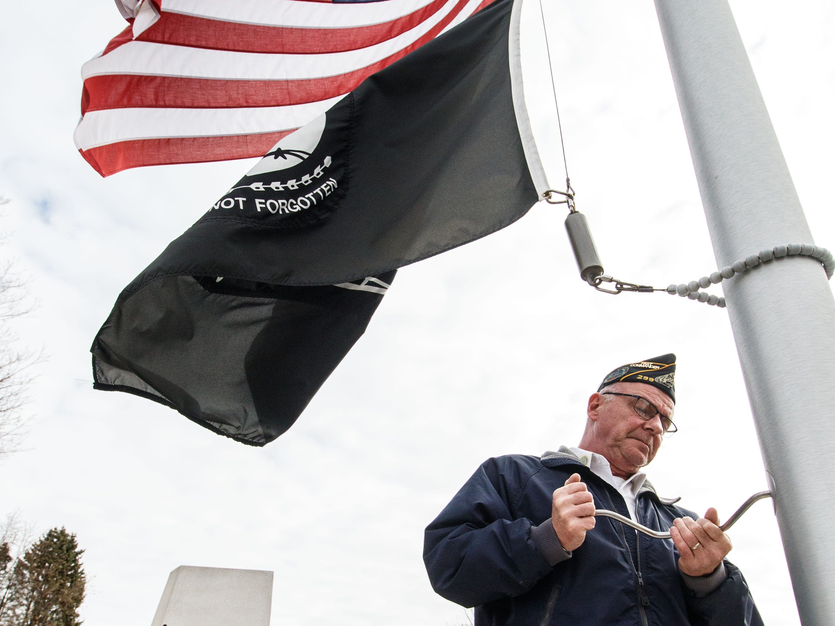 Joe Huber of American Legion Post 299 in Hales Corners lowers the flag to be retired during the flag changing ceremony at Hales Corners Park on Sunday, Nov. 11, 2018.