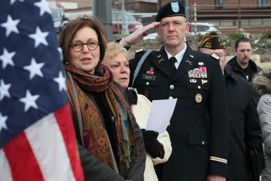 Wauwatosa Mayor Kathy Ehley (left) and the Rev. Mari Gabrielson sing the national anthem while Col. John T. Oakley of the Wisconsin National Guard salutes the flag at the ceremony.