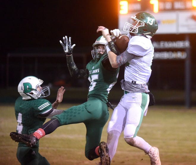 Yellville-Summit's Cody Dobbs hauls in a long pass over two Danville defenders on Friday night.