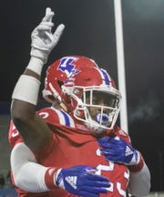 Louisiana Tech University's Jaqwis Dancy (23) celebrates after scoring a touchdown while DeVante Lovett (57) gives a hug during the game against Rice University at Joe Aillet Stadium in Ruston, La. on Nov. 10.