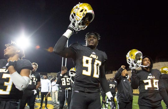 Despite the crushing loss, Alabama State's Lucky Oyovwi raises his helmet high during a team tradition at the end of the game.