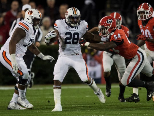 Auburn running back JaTarvious Whitlow (28) stiff arms Georgia linebacker Walter Grant (84) at Sanford Stadium in Athens, Ga., on Saturday, Nov. 10, 2018.