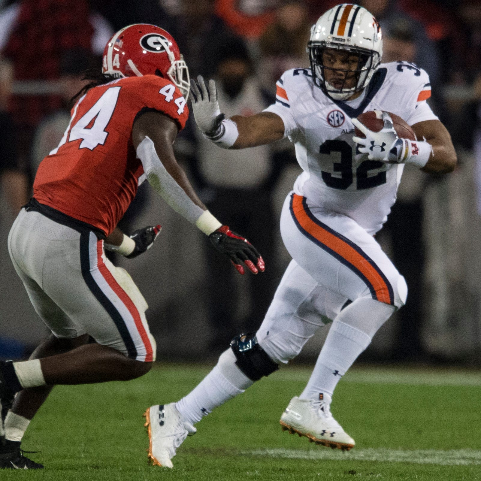 Auburn running back Malik Miller (32) stiff arms Georgia linebacker Juwan Taylor (44) at Sanford Stadium in Athens, Ga., on Saturday, Nov. 10, 2018. Georgia defeated Auburn 27-10.