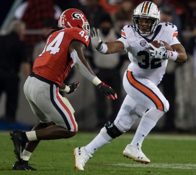 Auburn running back Malik Miller (32) stiff arms Georgia linebacker Juwan Taylor (44) at Sanford Stadium in Athens, Ga., on Saturday, Nov. 10, 2018. Georgia defeated Auburn 27-10.