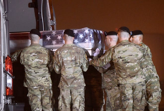 An Army carry team loads into a vehicle a transfer case containing the remains of Maj. Brent Taylor at Dover Air Force Base, Del., on Tuesday, Nov. 6, 2018.