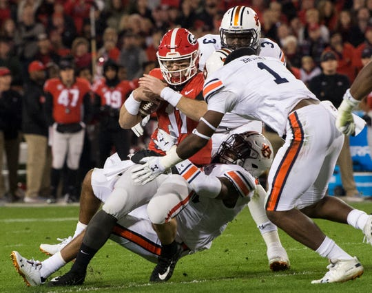 Auburn defensive lineman Big Kat Bryant (1) is called for targeting as he hits Georgia quarterback Jake Fromm (11) for a sack at Sanford Stadium in Athens, Ga., on Saturday, Nov. 10, 2018. Georgia leads Auburn 20-10 at halftime.