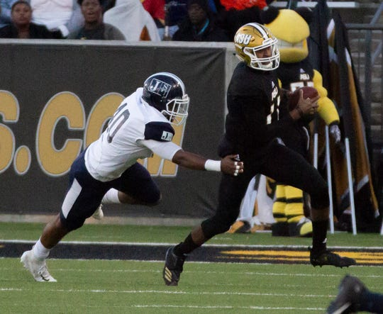 Alabama State's Chris Scott runs the ball as Jackson State's Keontre Hampton grabs at his hip for a tackle.