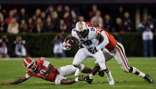 Auburn running back JaTarvious Whitlow (28) is tackled by Georgia linebacker D'Andre Walker (15) at Sanford Stadium in Athens, Ga., on Saturday, Nov. 10, 2018. Georgia leads Auburn 20-10 at halftime.