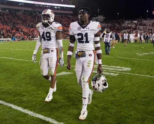 Auburn linebacker Darrell Williams (49) and defensive back Smoke Monday (21) walk off the field after the game at Sanford Stadium in Athens, Ga., on Saturday, Nov. 10, 2018. Georgia defeated Auburn 27-10.