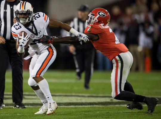 Auburn wide receiver Ryan Davis (23) slips away from Georgia defensive back Richard LeCounte (2) at Sanford Stadium in Athens, Ga., on Saturday, Nov. 10, 2018. Georgia leads Auburn 20-10 at halftime.