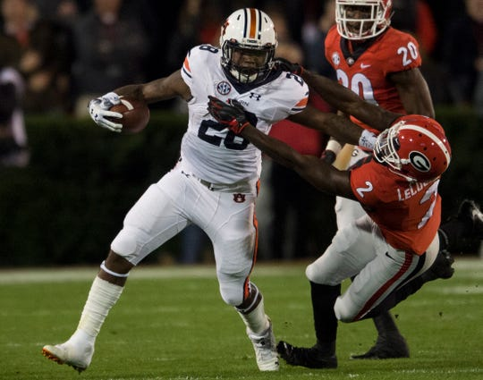 Auburn running back JaTarvious Whitlow (28) is dragged down by Georgia defensive back Richard LeCounte (2) at Sanford Stadium in Athens, Ga., on Saturday, Nov. 10, 2018.