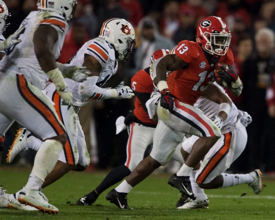 Georgia running back Elijah Holyfield (13) runs the ball down the field against  Auburn at Sanford Stadium in Athens, Ga., on Saturday, Nov. 10, 2018. Georgia leads Auburn 20-10 at halftime.