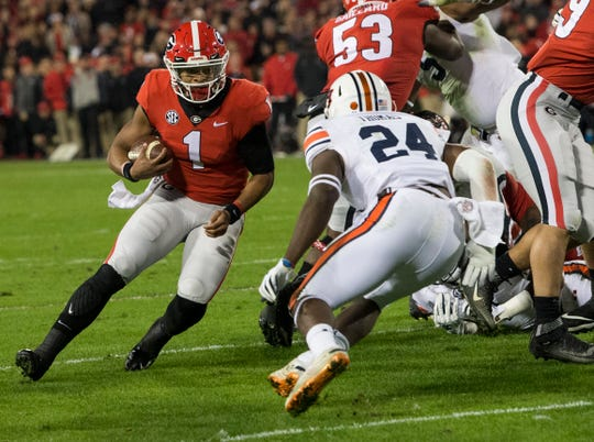 Georgia quarterback Justin Fields (1) runs the ball around his blocks against  Auburn at Sanford Stadium in Athens, Ga., on Saturday, Nov. 10, 2018. Georgia leads Auburn 20-10 at halftime.