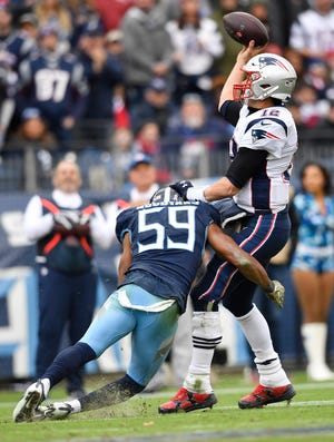 Titans inside linebacker Wesley Woodyard (59) hits Patriots quarterback Tom Brady (12) as he throws in the second half Sunday.