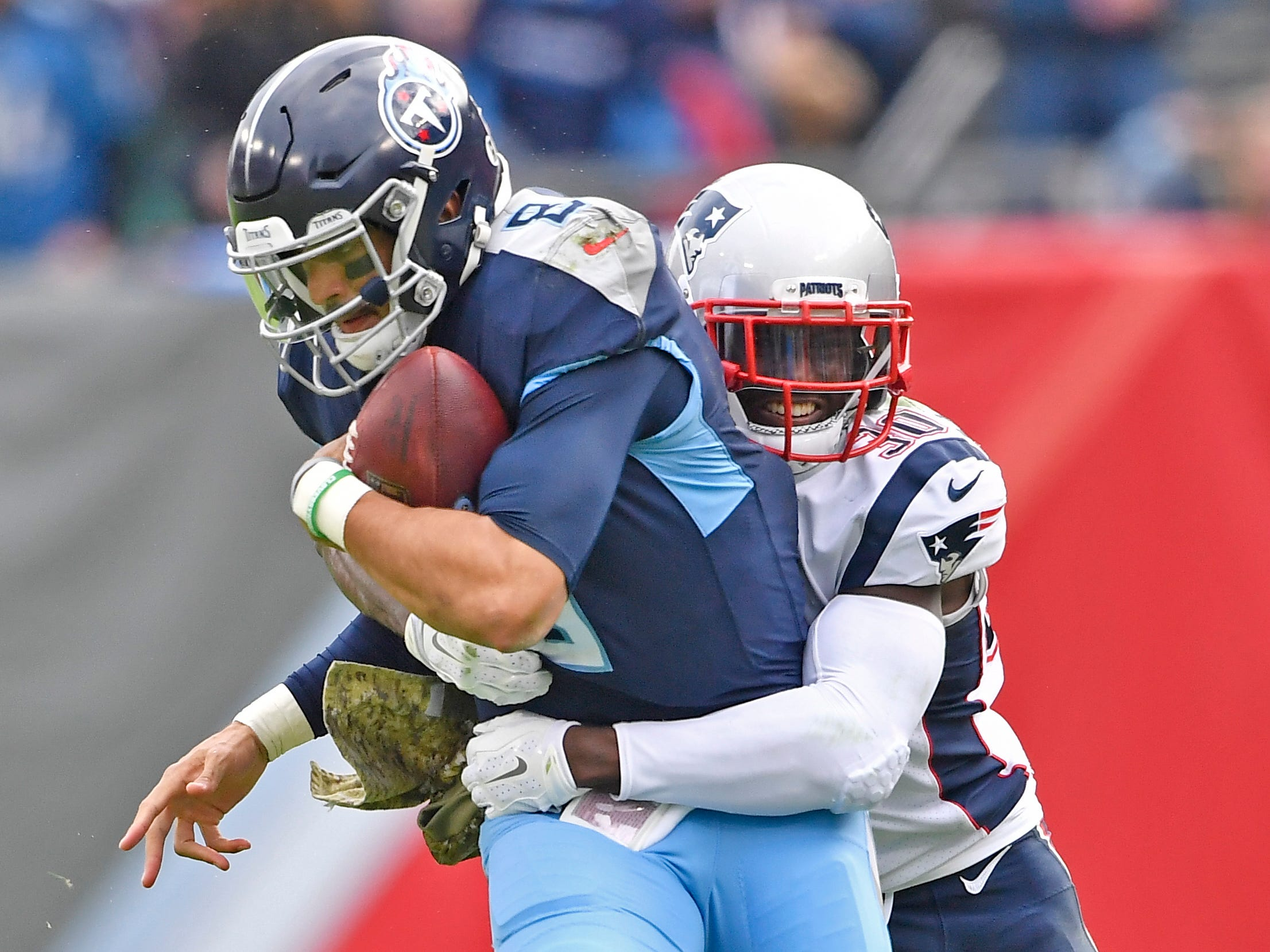 Titans quarterback Marcus Mariota (8) pulls in a catch from wide receiver Darius Jennings (15) and is stopped by Patriots cornerback Jason McCourty (30) in the second half at Nissan Stadium Sunday, Nov. 11, 2018, in Nashville, Tenn.