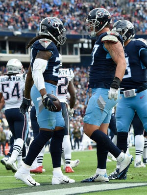 Titans running back Derrick Henry (22) celebrates his touchdown with offensive tackle Taylor Lewan (77) in the second quarter Sunday.