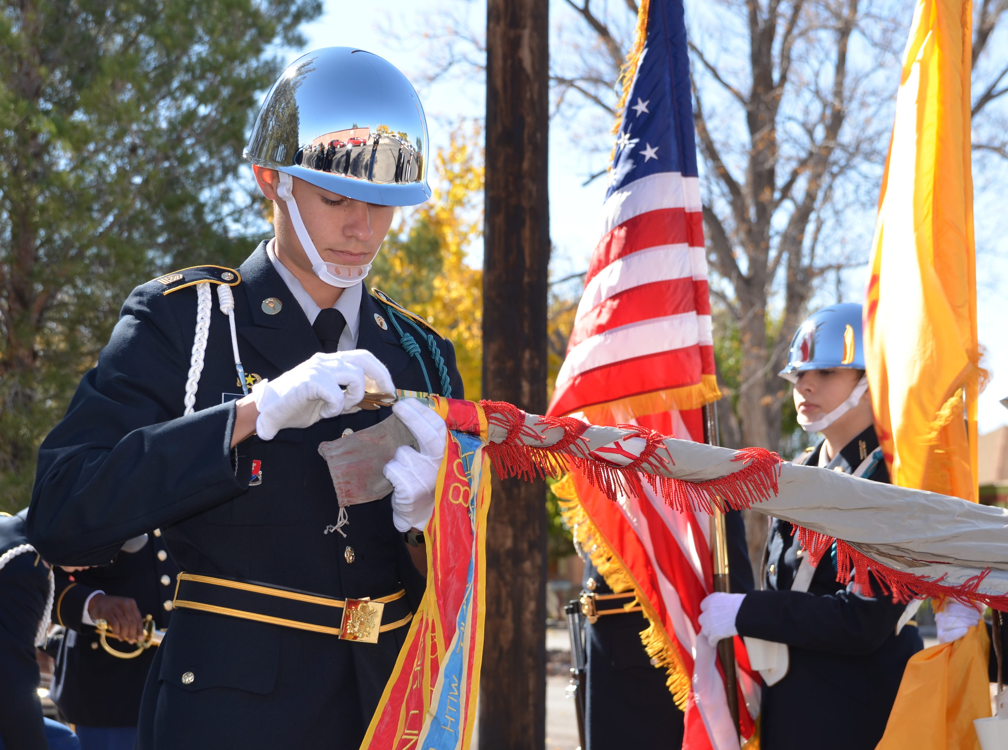 John Denning, 16, A junior at Deming High School and commander of DHS Color Guard unrolls the Deming High ROTC flag.