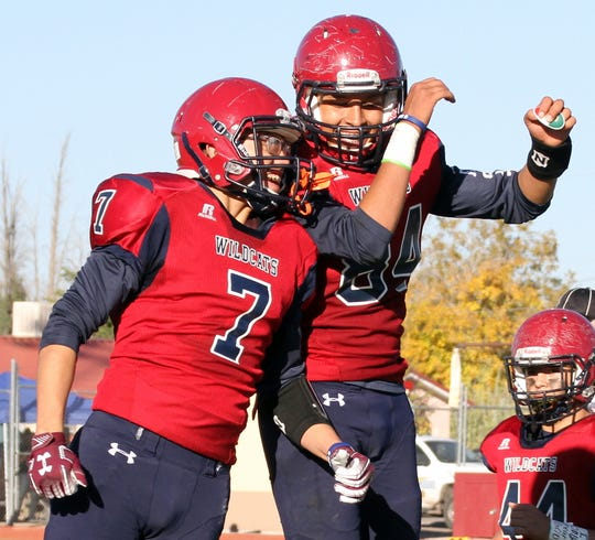 "Juniors Israel Reyes (7) and senior Johnathan Ledezma (84) celebrate following the Wildcats 38-28 playoff win over the Scorpions with the ""'Cat Bump."""