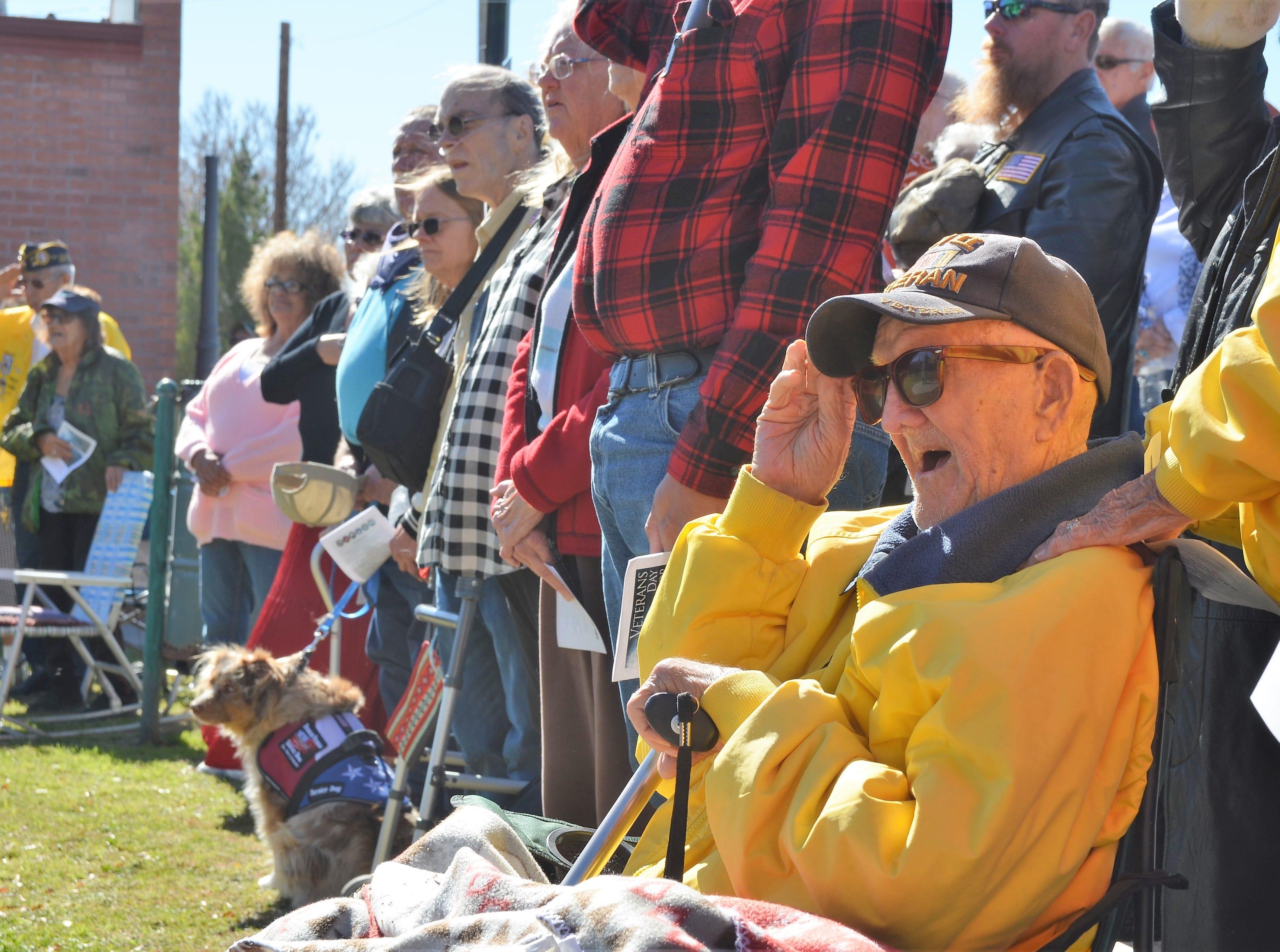Irving Rutto, 91, a World War II Navy veteran salutes the flags.
