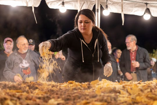 Susanna Martinez, employee at Dickerson's Catering, puts cheese on top of the huge nacho platter at Noche de Nachos. Las Cruces unofficially set the record for world's largest serving of nachos Saturday, Nov. 10, 2018, in downtown Las Cruces.