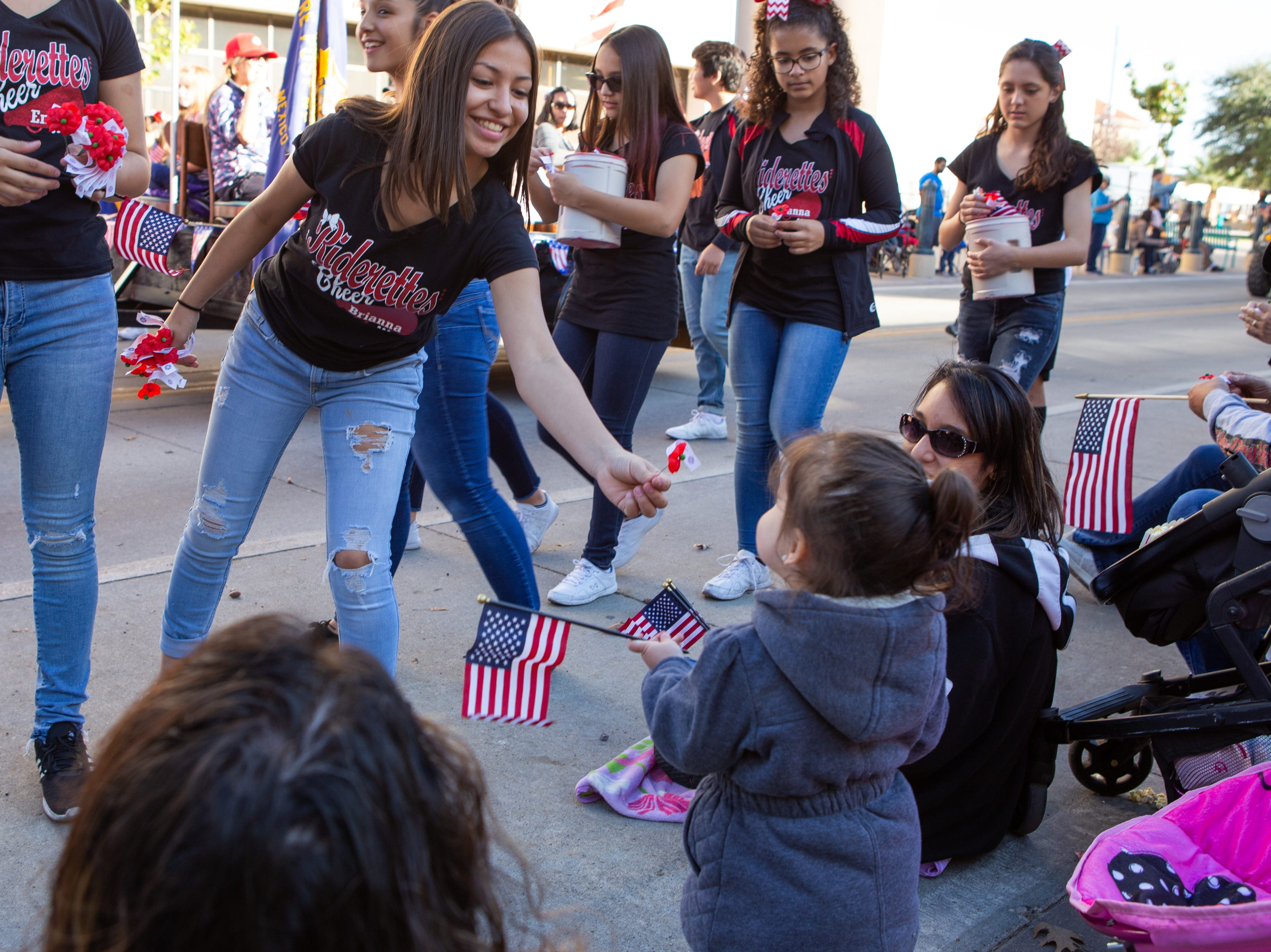 Riderette Cheer Team member Briana Ramirez, 13, hands a poppy to Zoey Hernandez, 2, during the Veterans Day Parade held on November 10, 2018.