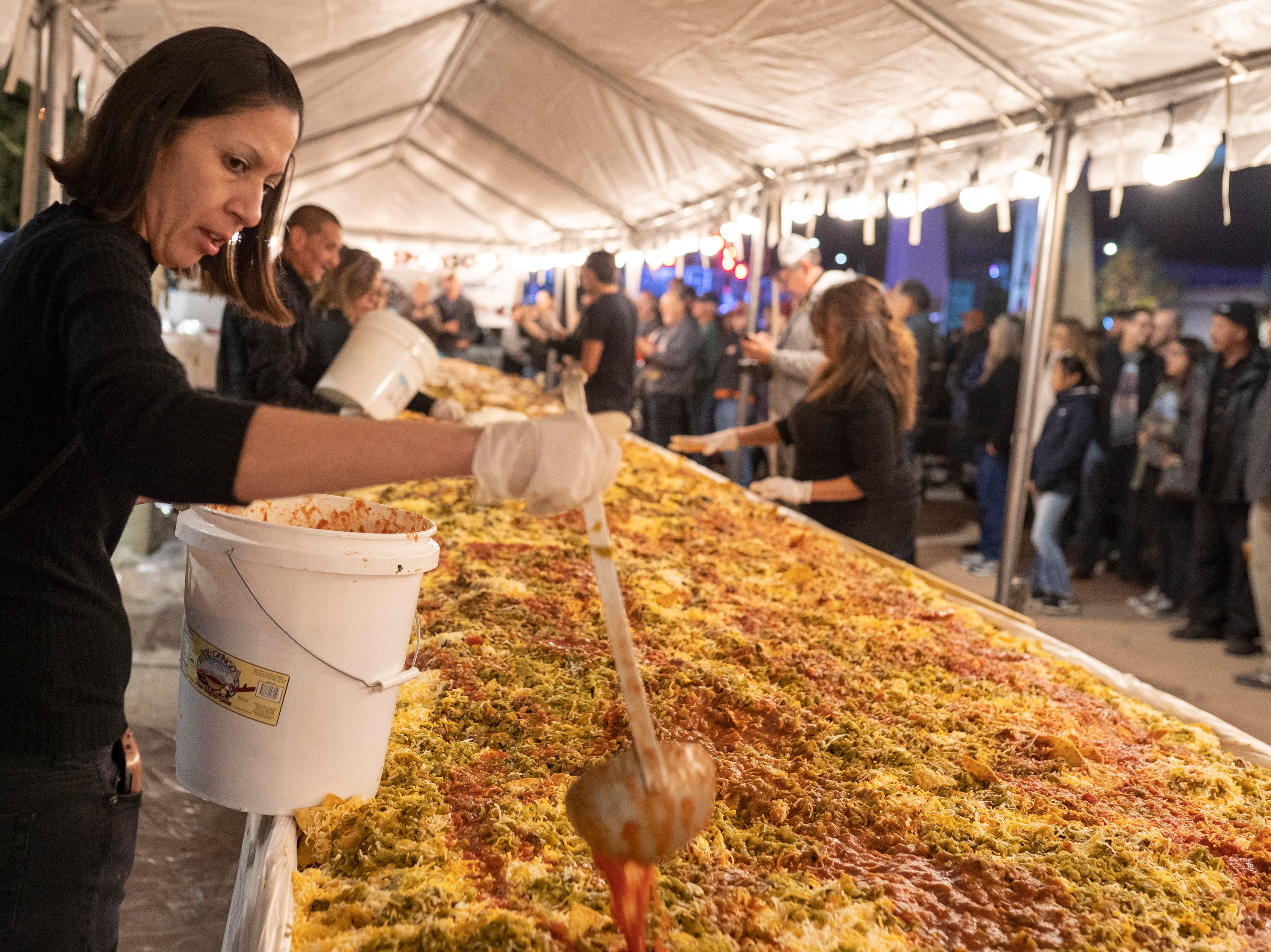 Dickerson's Catering employees mix nacho ingredients at Noche de Nachos. Las Cruces unofficially set the record for world's largest serving of nachos Saturday, Nov. 10, 2018, in downtown Las Cruces.