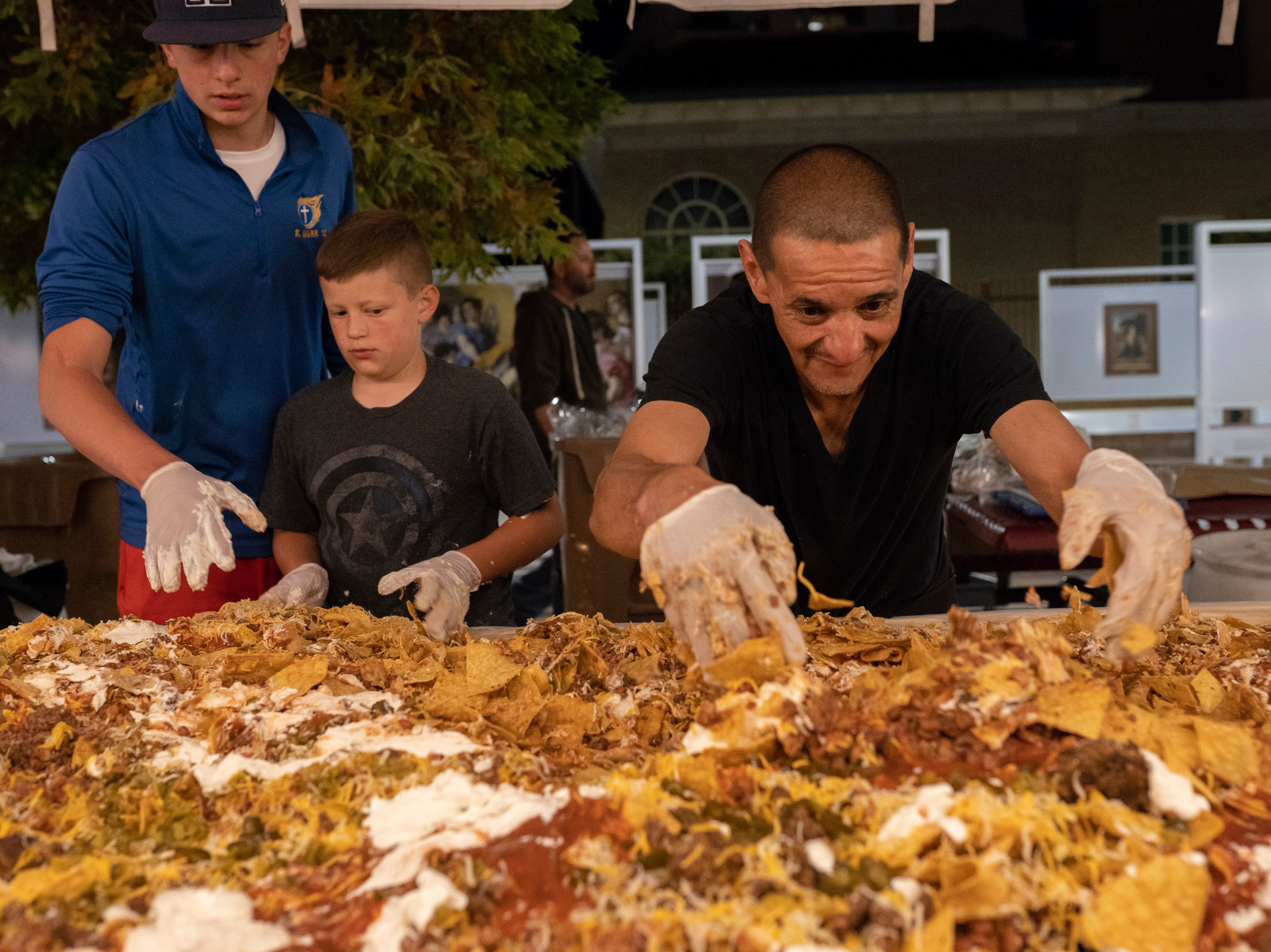 Event staff mix nacho ingredients during Noche de Nachos. Las Cruces unofficially set the record for world's largest serving of nachos Saturday, Nov. 10, 2018, in downtown Las Cruces.