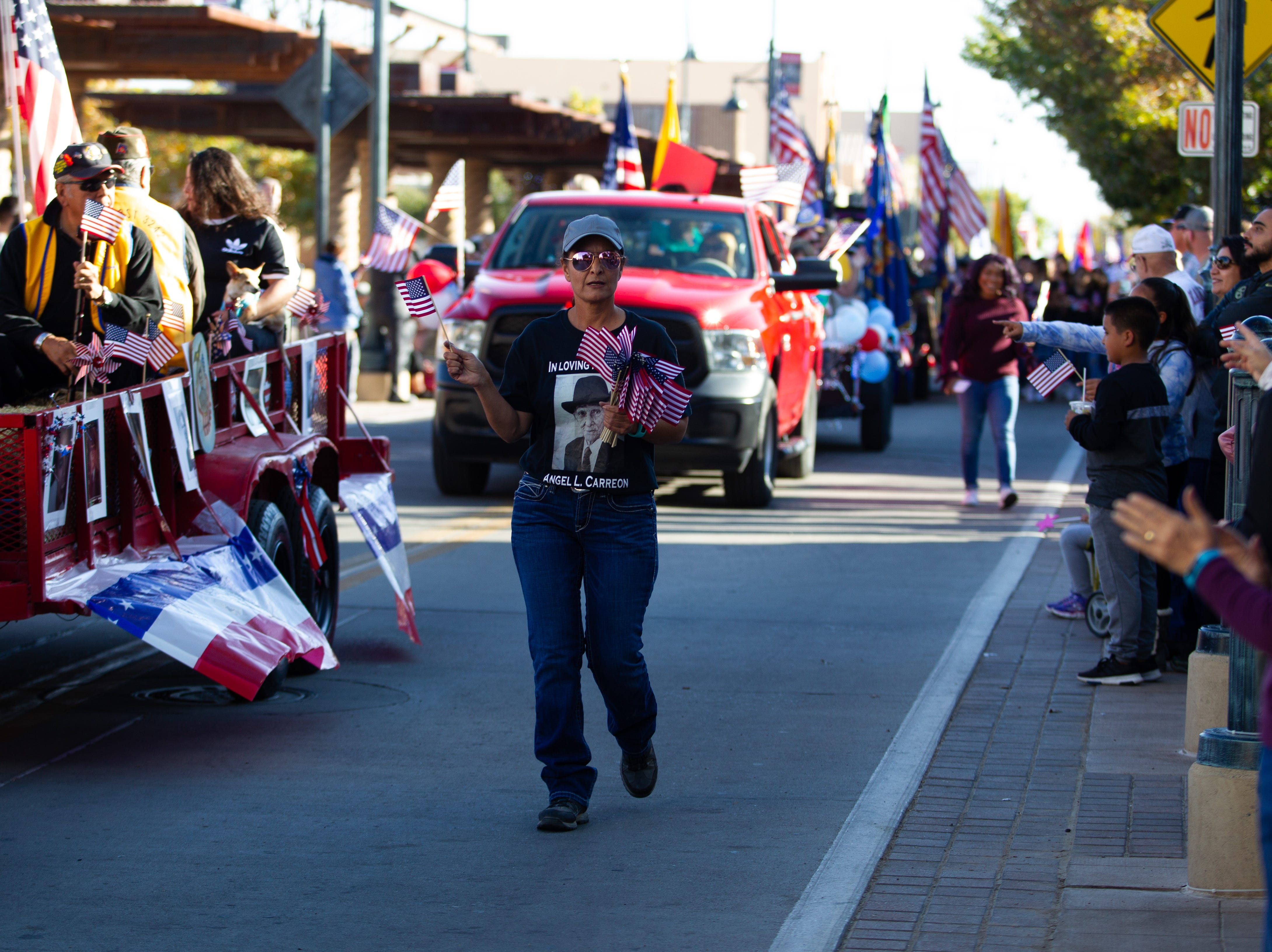 Virginia Carreon hands out US Flags to spectators during the Veterans Day Parade held on November 10, 2018.