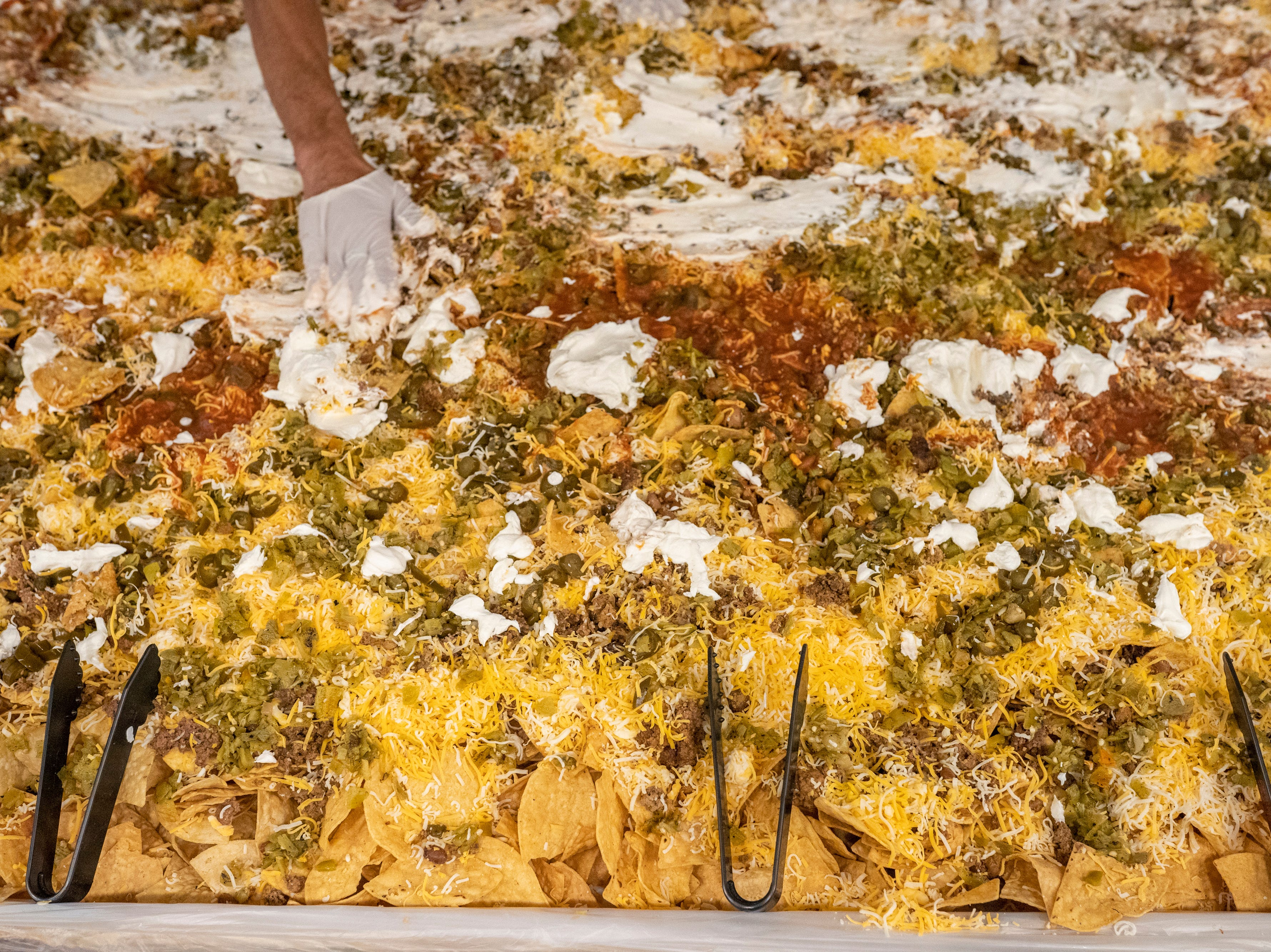 Tongs are placed atop the gigantic pile of nachos, showing visitors the nachos are ready to eat. Las Cruces unofficially set the record for world's largest serving of nachos Saturday, Nov. 10, 2018, in downtown Las Cruces.