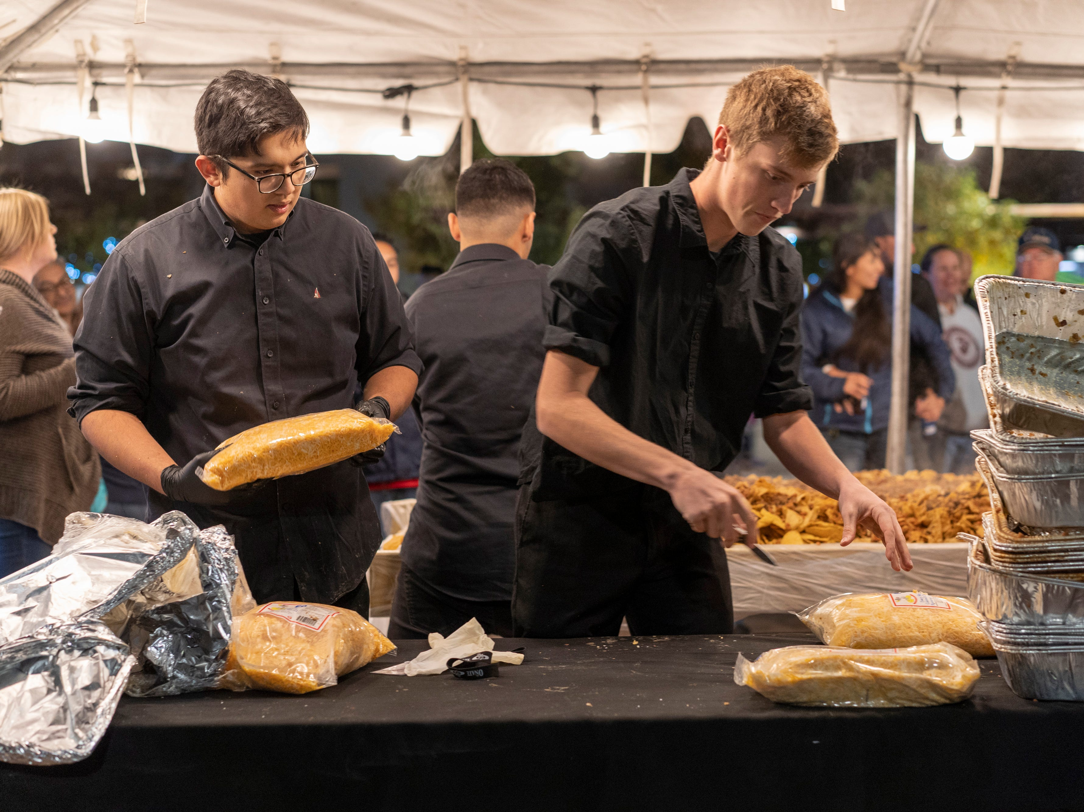 Dickerson's Catering employees get cheese ready for Noche de Nachos. Las Cruces unofficially set the record for world's largest serving of nachos Saturday, Nov. 10, 2018, in downtown Las Cruces.