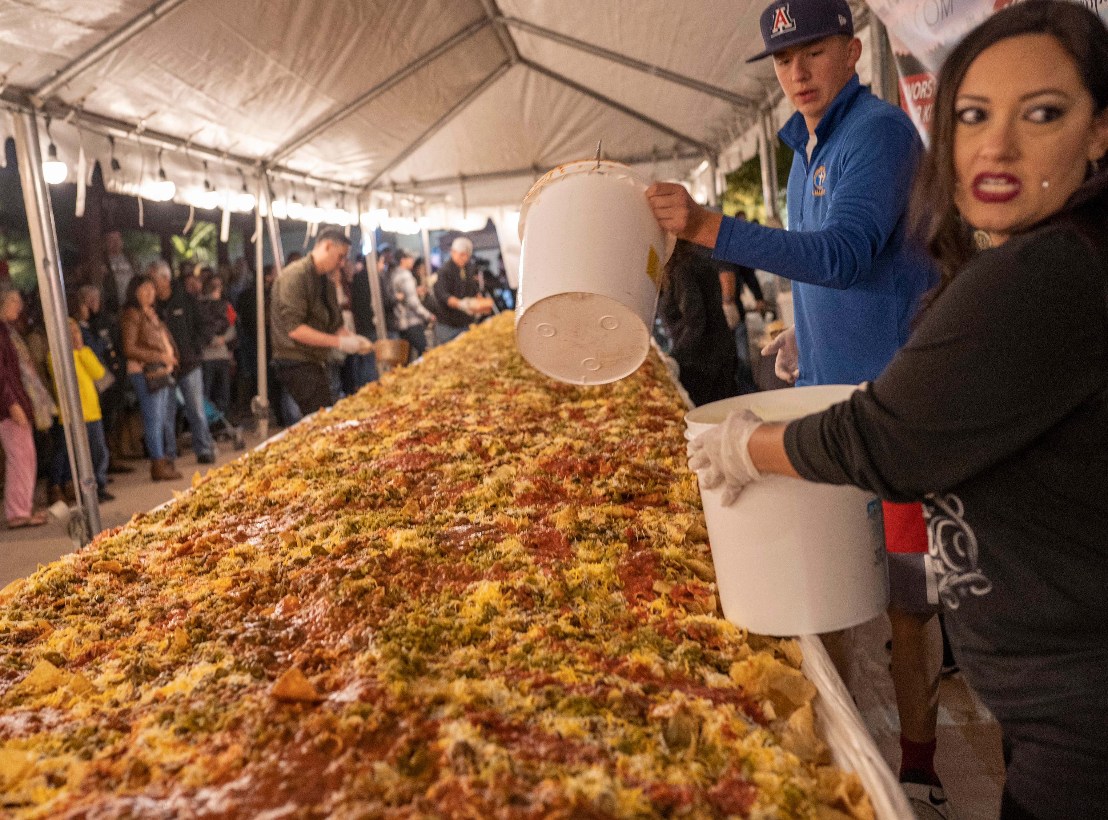 Dickerson's Catering employees put toppings on the gigantic platter of nachos at Noche de Nachos. Las Cruces unofficially set the record for world's largest serving of nachos Saturday, Nov. 10, 2018, in downtown Las Cruces.