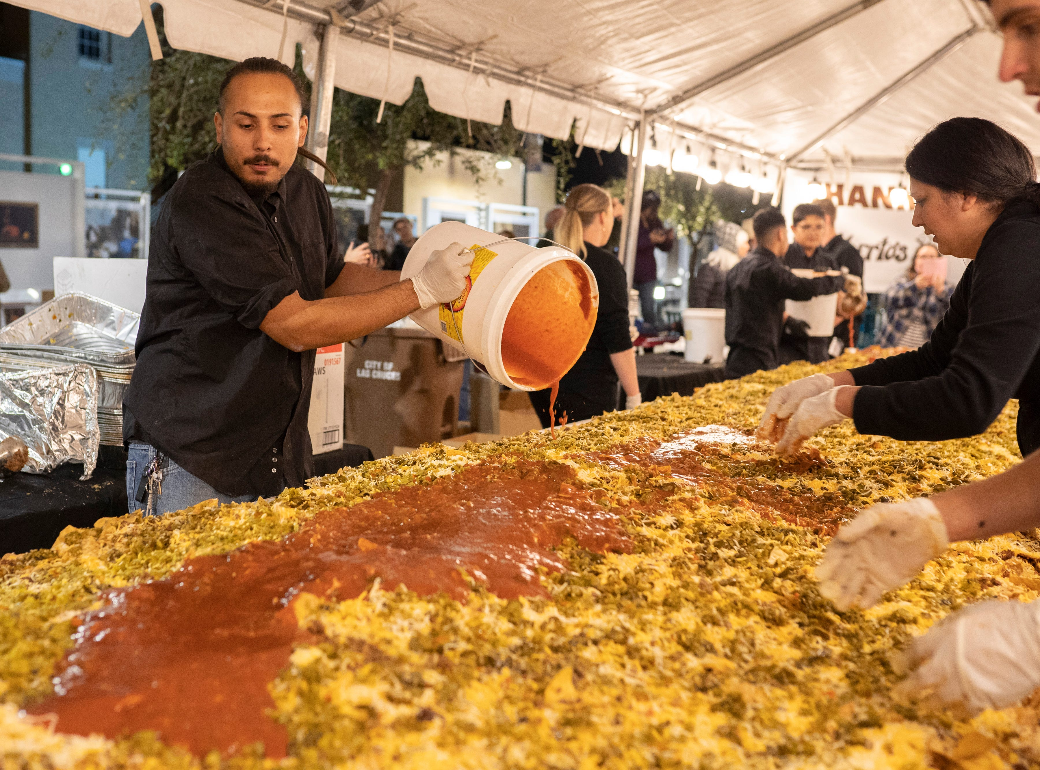Dickerson's Catering employees mix nacho ingredients together at Noche de Nachos. Las Cruces unofficially set the record for world's largest serving of nachos Saturday, Nov. 10, 2018, in downtown Las Cruces.