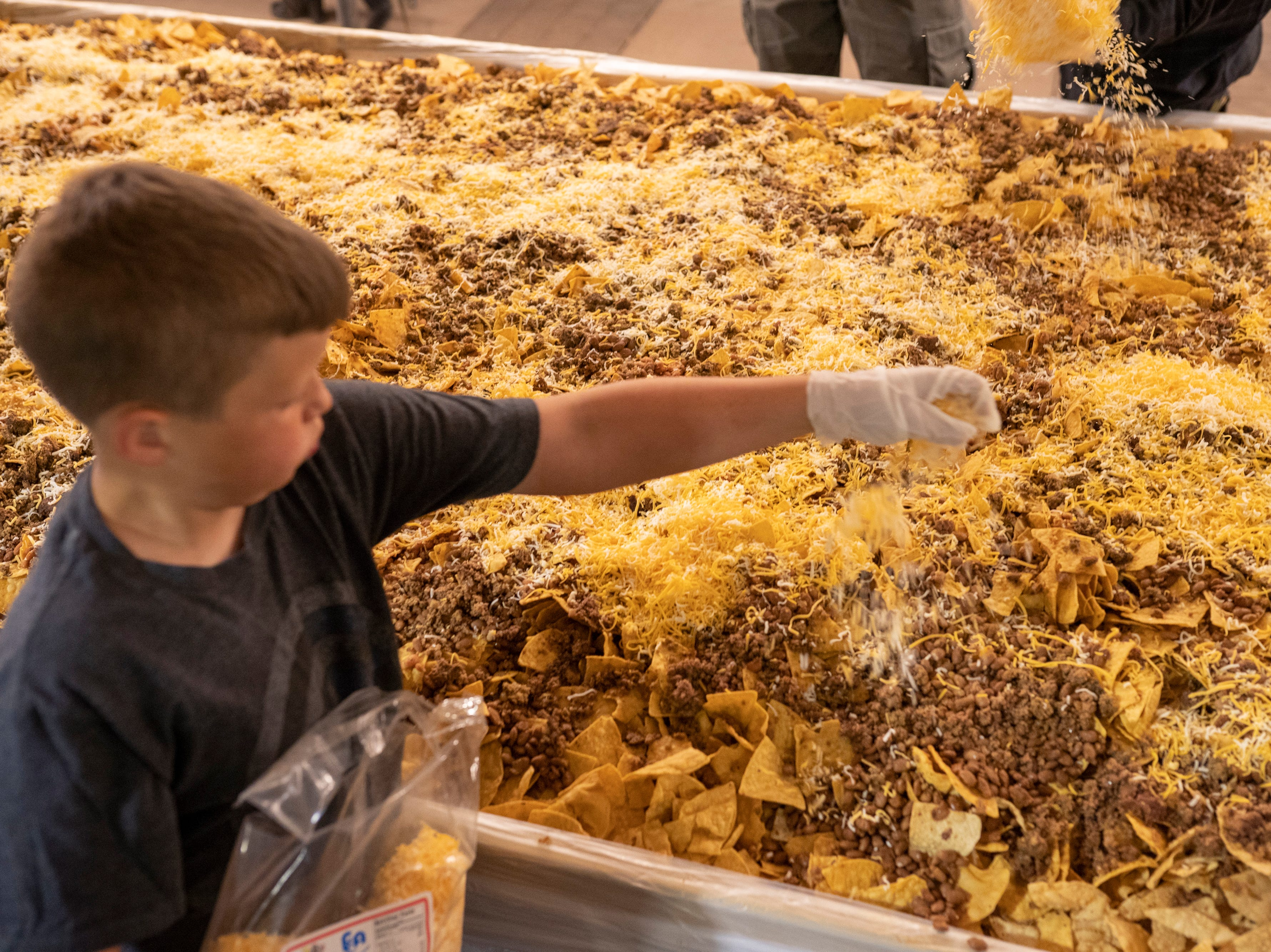 Weston Marr, 9, puts cheese on top of the nachos at Noche de Nachos. Las Cruces unofficially set the record for world's largest serving of nachos Saturday, Nov. 10, 2018, in downtown Las Cruces.