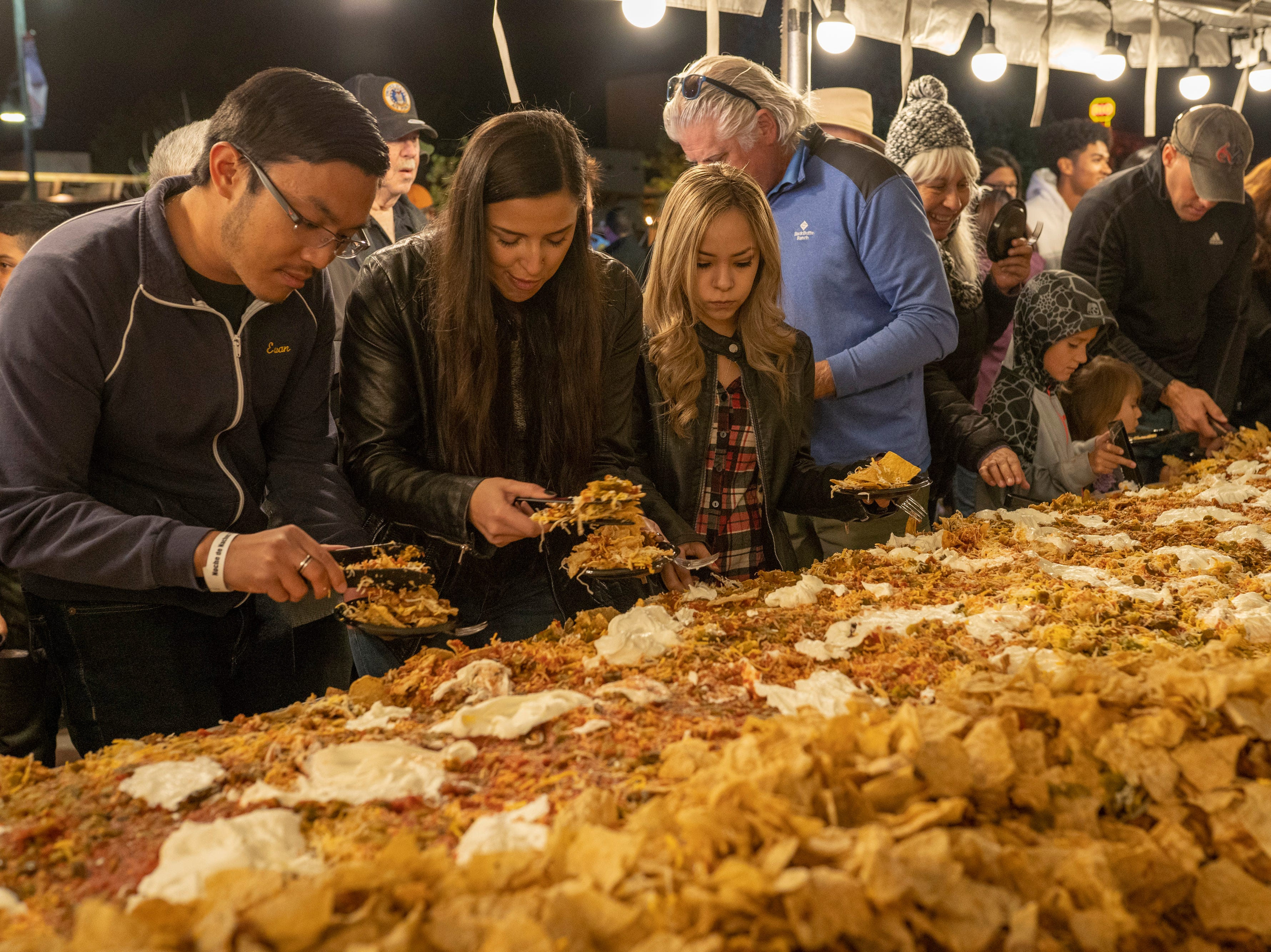 Attendees dig into the gigantic platter of nachos at Noche de Nachos. Las Cruces unofficially set the record for world's largest serving of nachos Saturday, Nov. 10, 2018, in downtown Las Cruces.