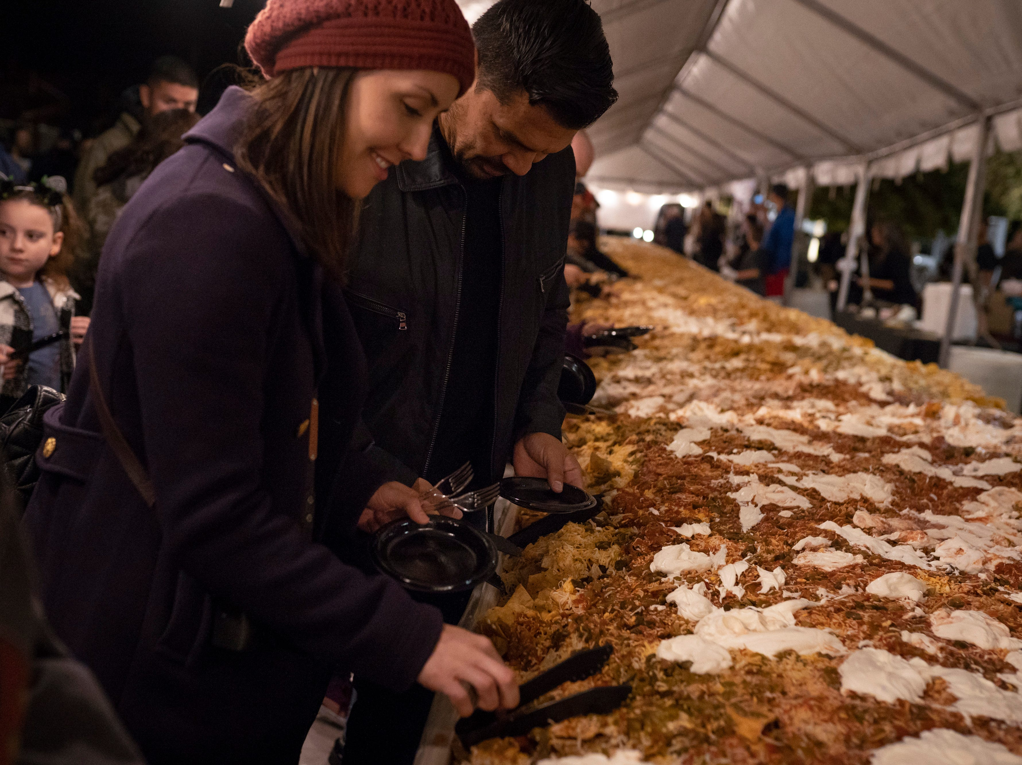 Visitors to Noche de Nachos take the first plates of nachos after Las Cruces unofficially set the record for world's largest serving of nachos Saturday, Nov. 10, 2018, in downtown Las Cruces.