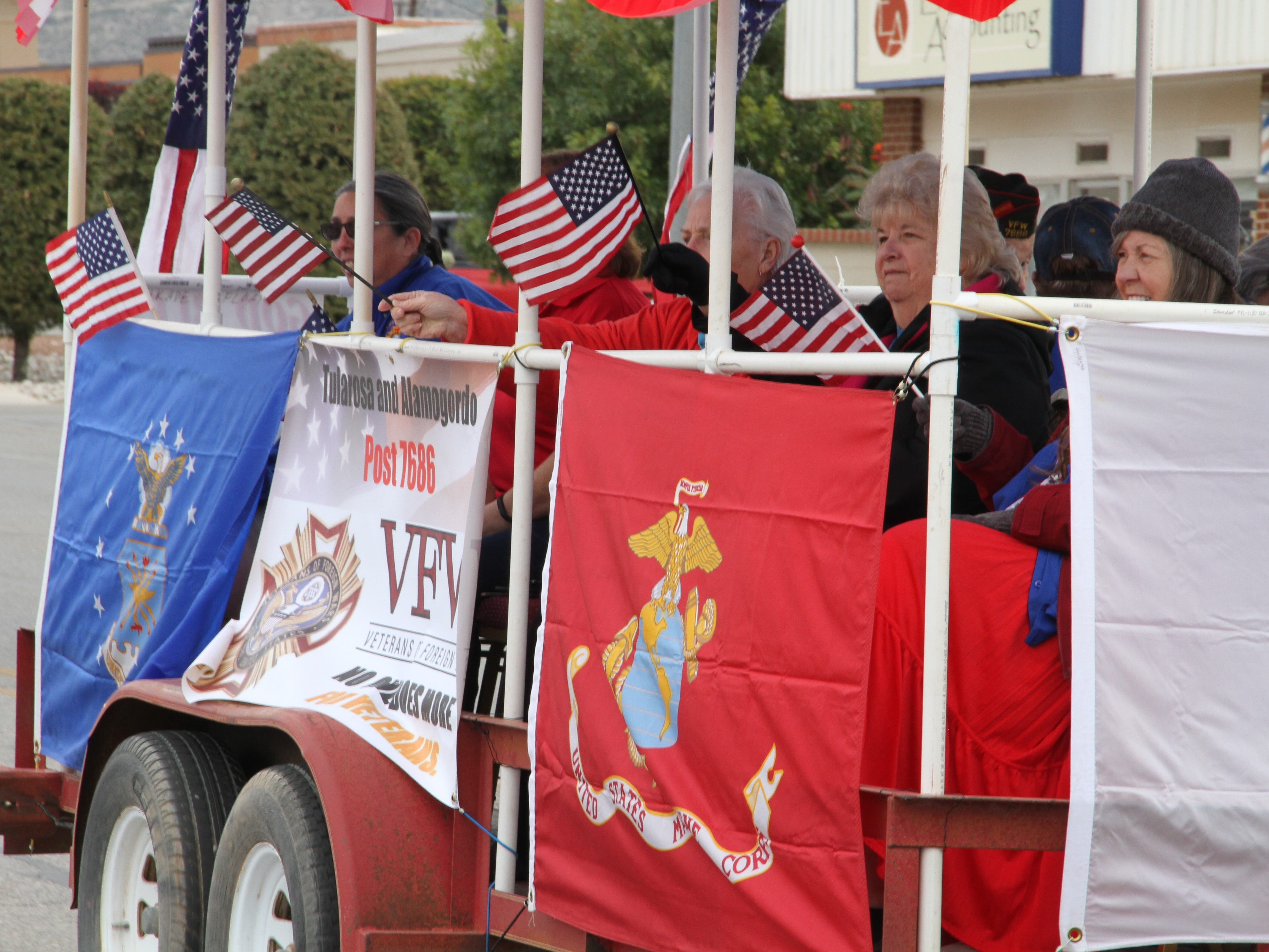 VFW Post 7686 float riders waived flags during the Alamogordo Veterans Day Parade Saturday.