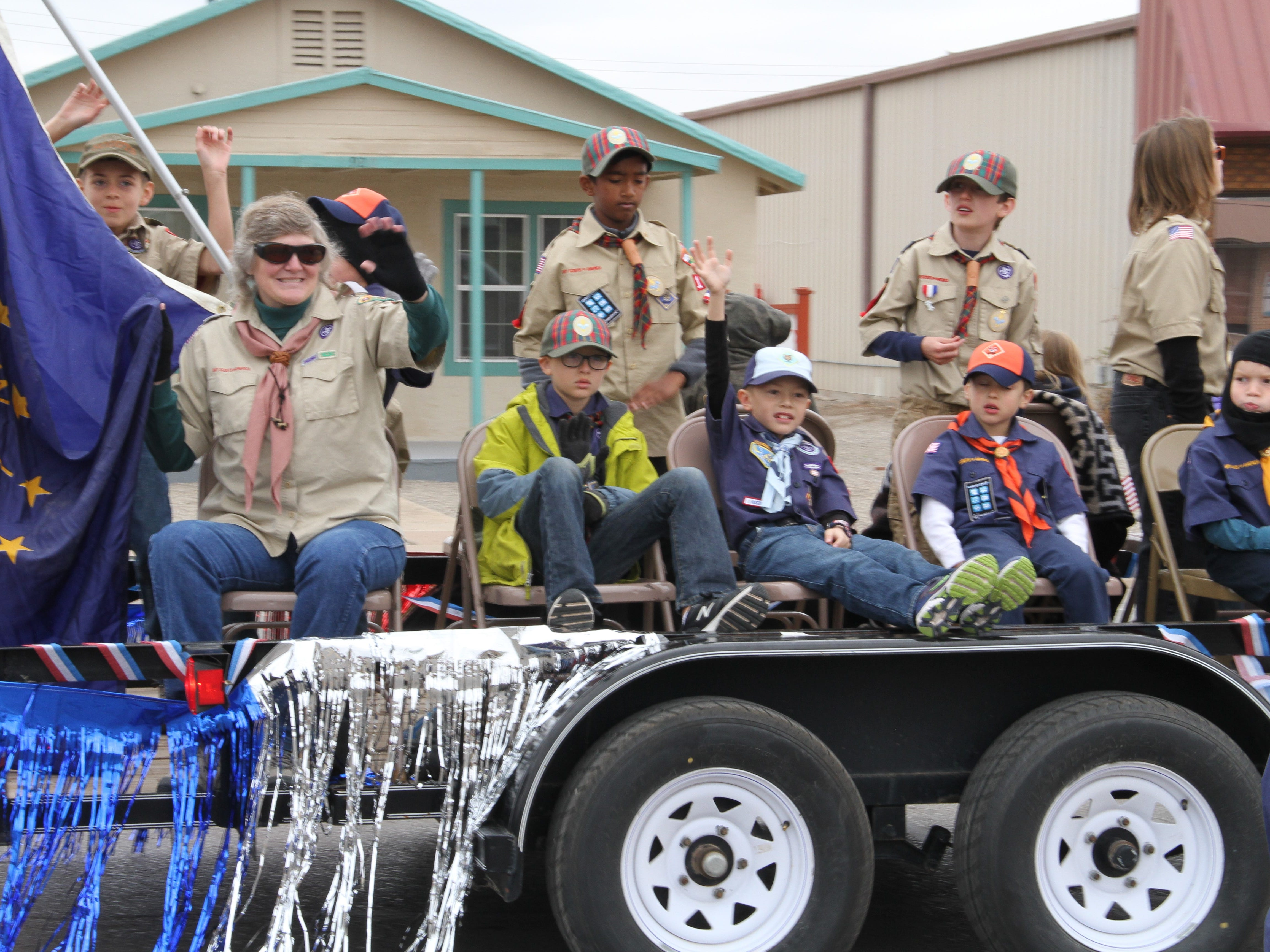 The Boy Scouts and Cub Scouts waive to the crowd during Alamogordo's Veterans Day Parade Saturday.