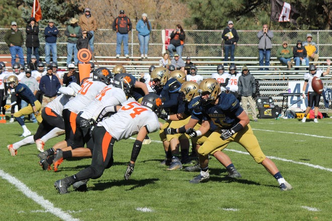 Ruidoso's offensive line looks to fend off Aztec's defensive front after snapping the ball during Saturday's 4A playoff opener in Ruidoso. The Tigers won, 40-19.