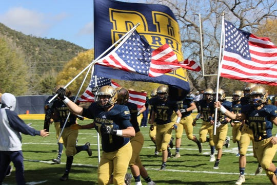 Ruidoso Warriors run with the American flag proudly representing the team.