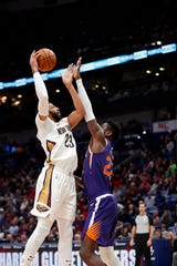 New Orleans Pelicans forward Anthony Davis (23) shoots against Phoenix Suns center Deandre Ayton (22). (AP Photo/Gerald Herbert)