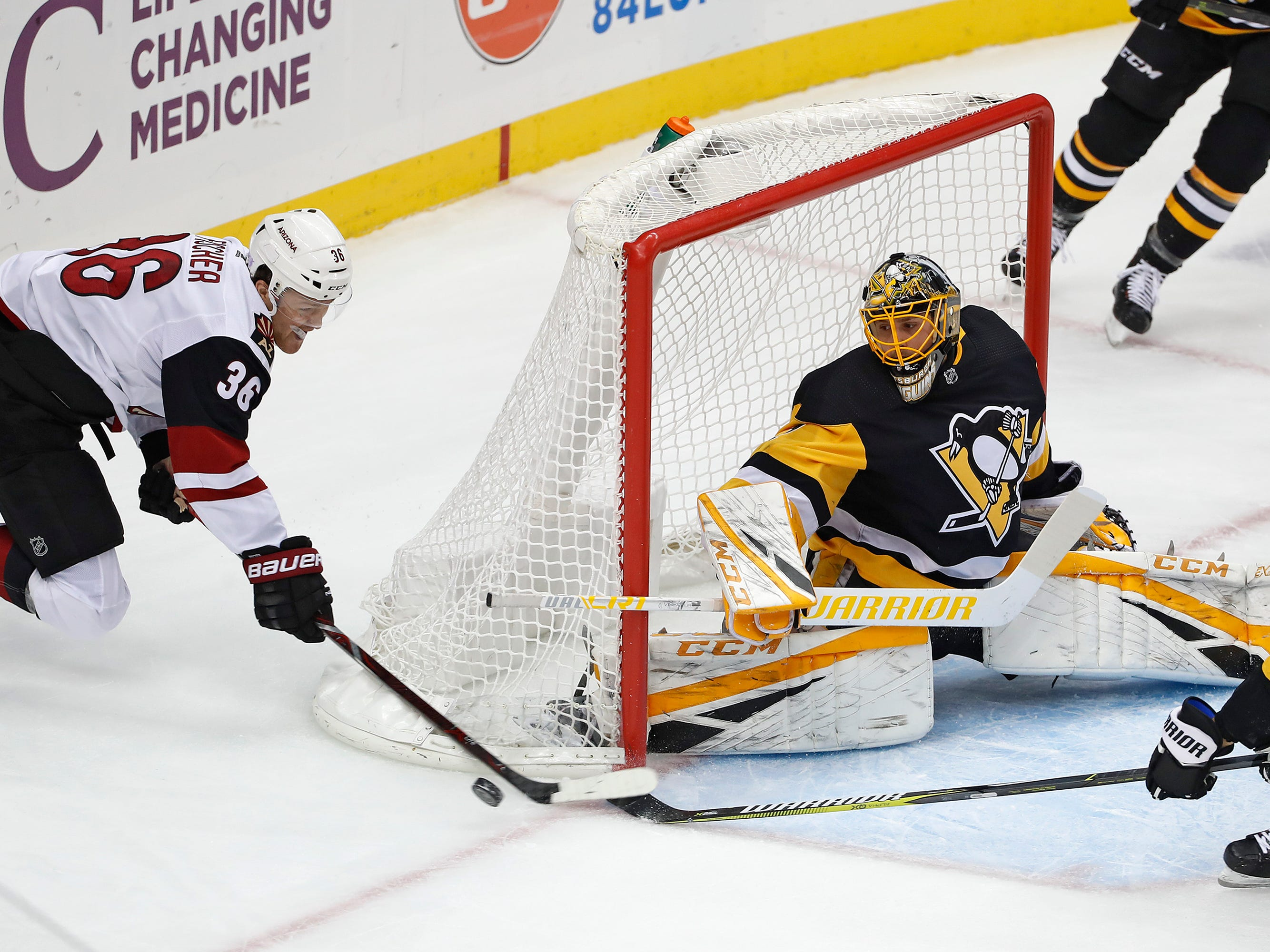 Pittsburgh Penguins goaltender Casey DeSmith (1) and teammate Brian Dumoulin (8) block a shot by Arizona Coyotes' Christian Fischer (36) during the first period of an NHL hockey game in Pittsburgh, Saturday, Nov. 10, 2018. (AP Photo/Gene J. Puskar)