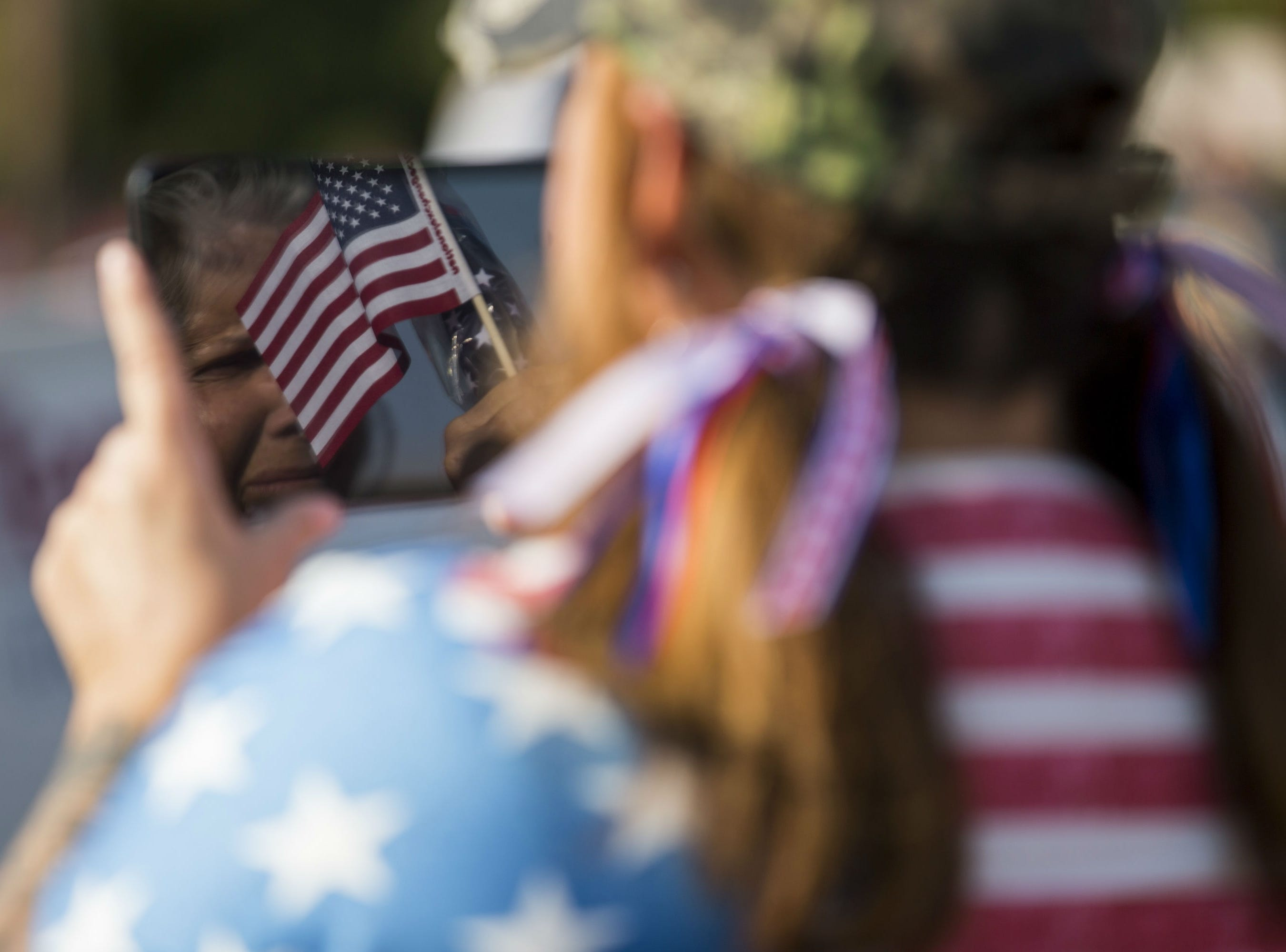 Linda Guariglio is seen in the reflection of Stephanie Guariglio's screen during the Veterans Day Parade on Nov. 11, 2018, in Tempe, Ariz.
