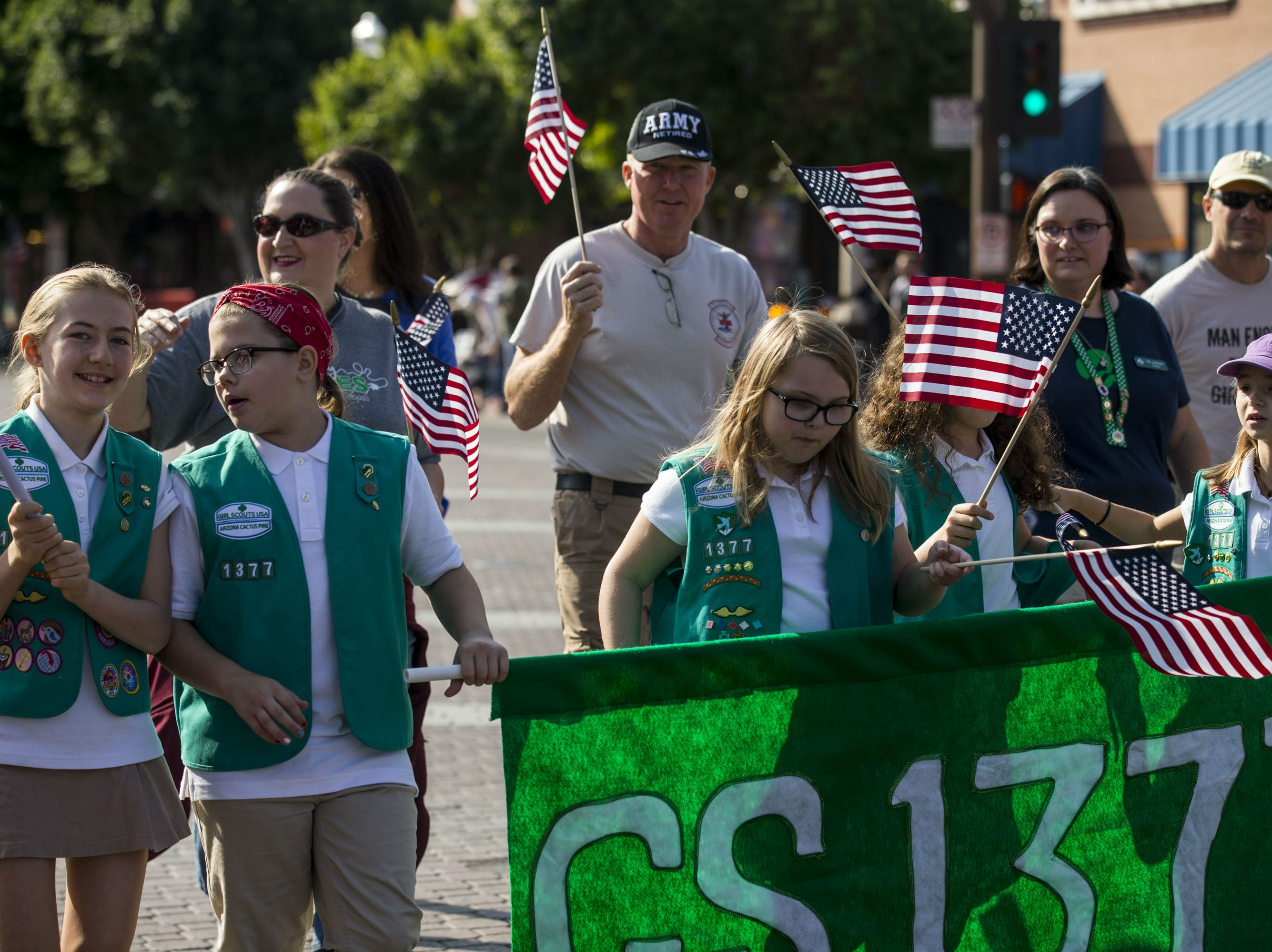 Girl Scouts walk on Mill Avenue during the Veterans Day Parade on Nov. 11, 2018, in Tempe, Ariz.