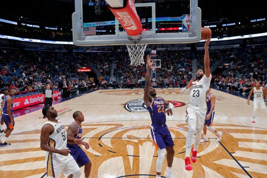 New Orleans Pelicans forward Anthony Davis (23) goes to the basket against Phoenix Suns center Deandre Ayton (22) in the first half of an NBA basketball game in New Orleans, Saturday, Nov. 10, 2018. (AP Photo/Gerald Herbert)